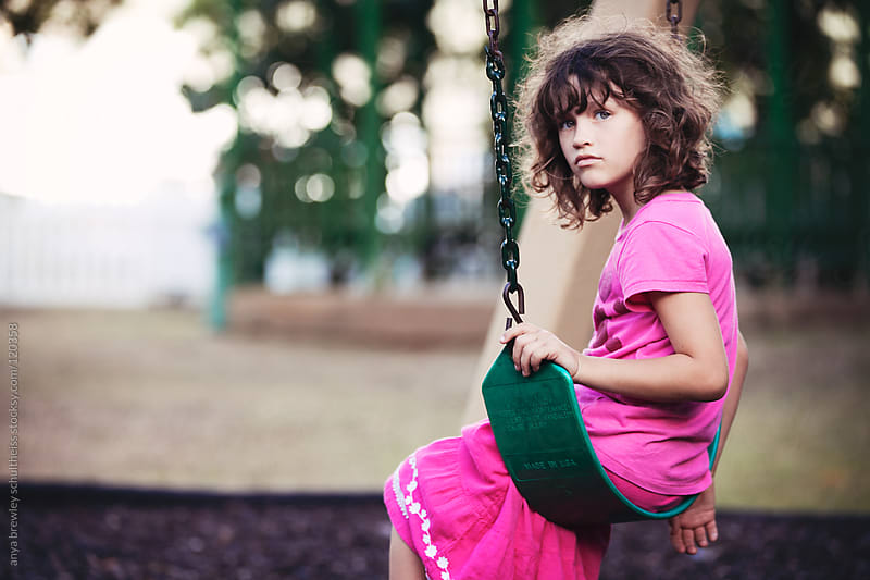 Girl in pink sitting thoughtfully on a swing by anya brewley schultheiss for Stocksy United