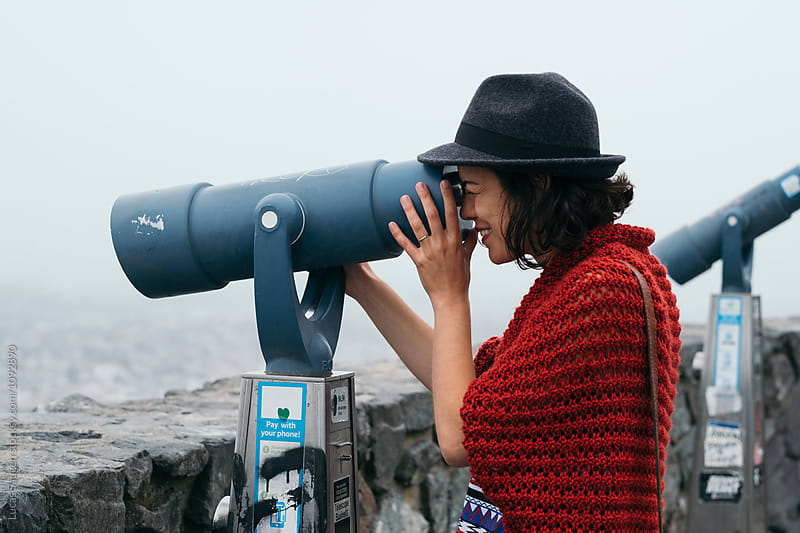 smiling tourist watching cityscape through binocular by Lucas Saugen for Stocksy United