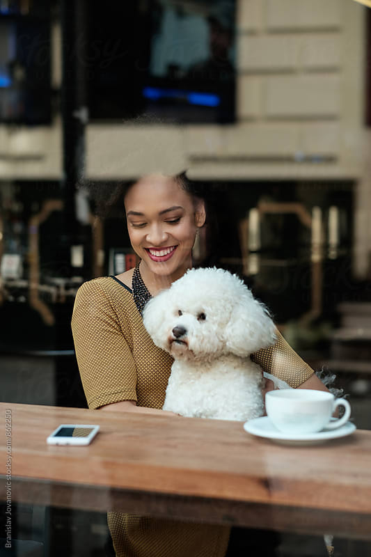 Beautiful Young Woman Sitting at the Cafe with her Dog by Branislav Jovanović for Stocksy United