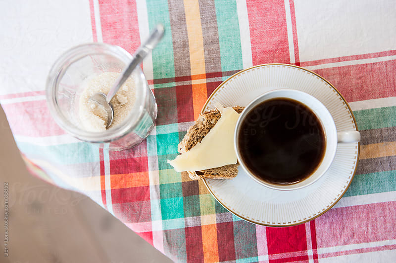 Black coffee and cheese on toast from above on checkered tablecl by Lior + Lone for Stocksy United