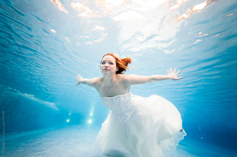Trash the Dress Underwater Beautiful Bride Swimming in Wedding Dress by JP Danko for Stocksy United
