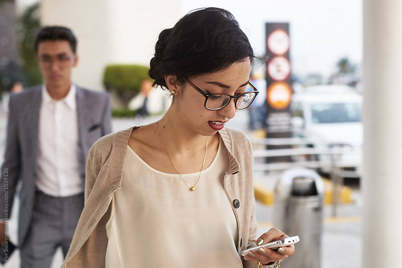 Young woman checking her cellphone while walking outside airport by Per Swantesson for Stocksy United