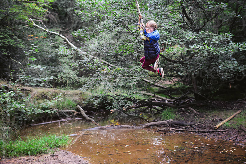 Boy on a rope swing. by Kirstin Mckee for Stocksy United
