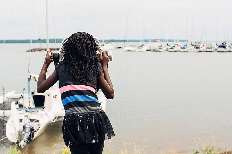 Black girl looking through binoculars by a lake shore by Gabriel (Gabi) Bucataru for Stocksy United
