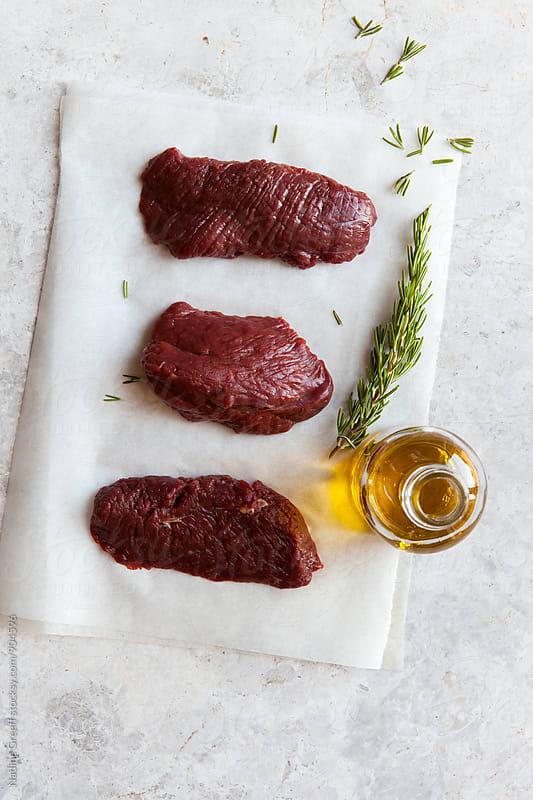 Raw steaks with seasonings by Nadine Greeff for Stocksy United