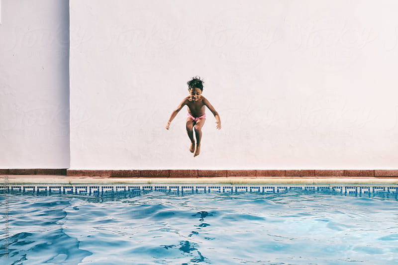 A little boy jumping to a swimming pool by Bisual Studio for Stocksy United