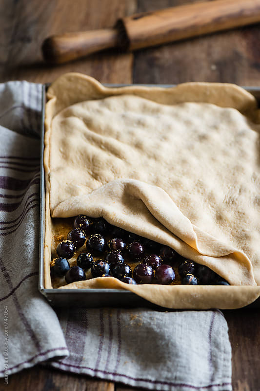 preparing homemade sweet focaccia stuffed with black grape by Laura Adani for Stocksy United