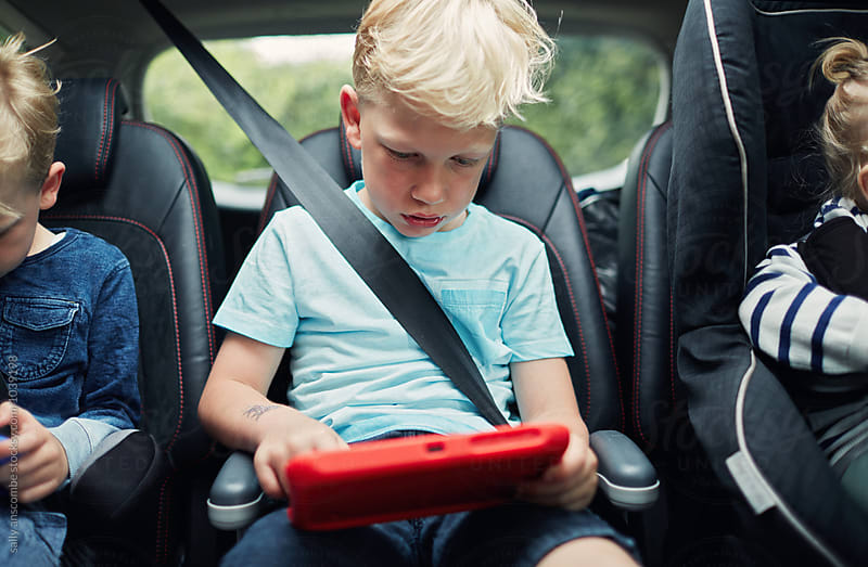 Children using electronic tablets in the car by sally anscombe for Stocksy United
