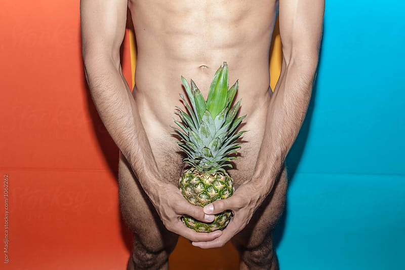 guy hiding with pineapple private parts in front of the colorful background, youth, crazy, summer, party by Igor Madjinca for Stocksy United