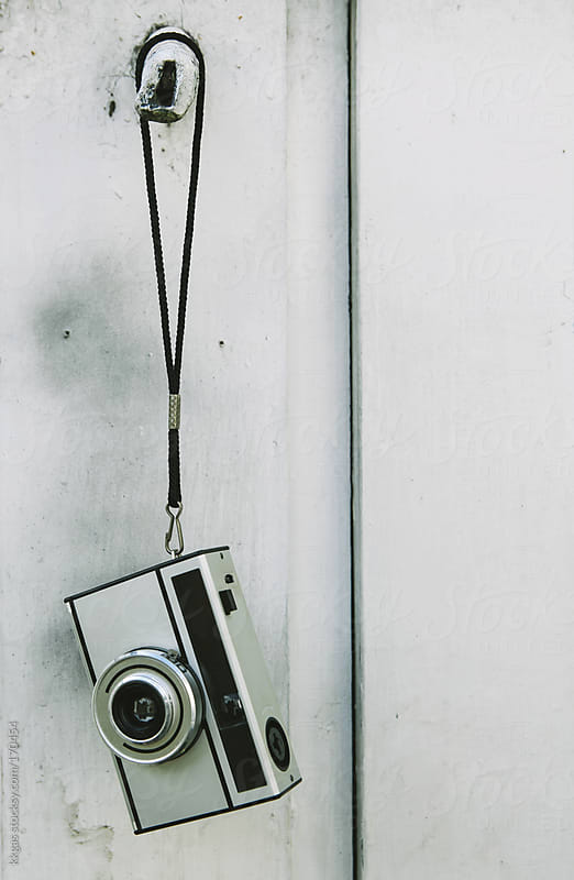 Retro camera hanging against white wooden background by kkgas for Stocksy United