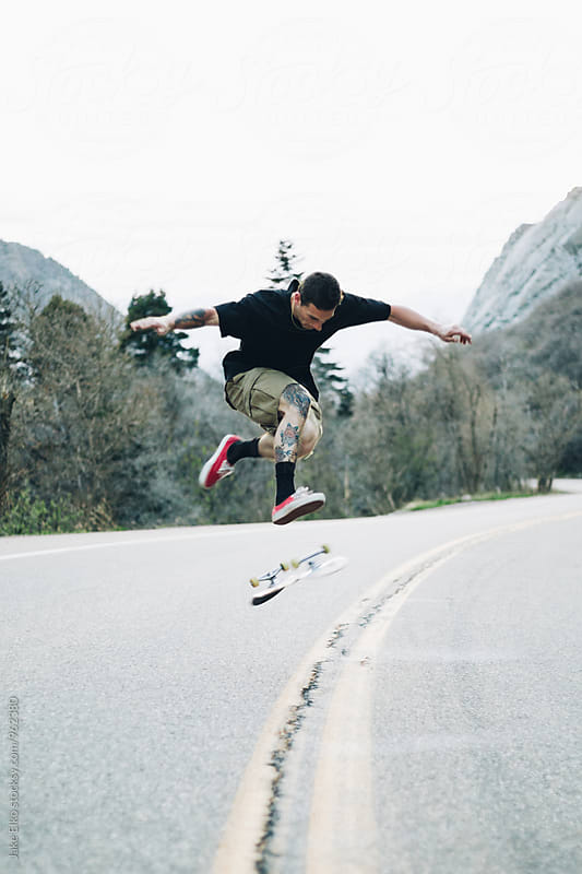 Skateboarder 360 Flip Canyon Road by Jake Elko for Stocksy United