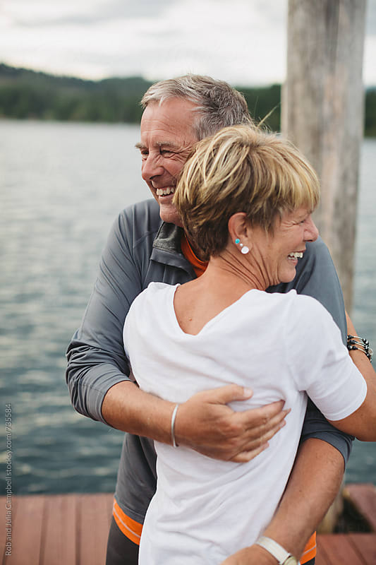 Happy older couple hugging and laughing in a real moment by Rob and Julia Campbell for Stocksy United