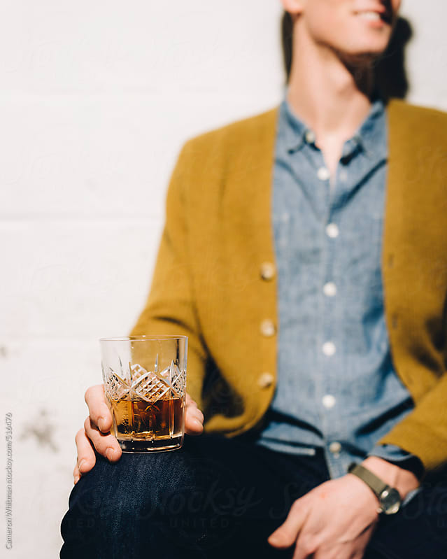 Young man drinking Scotch with a smile by Cameron Whitman for Stocksy United