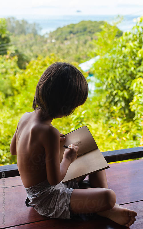 Small boy learning/writing his homework  in the middle of the jungle. by Marko Milanovic for Stocksy United