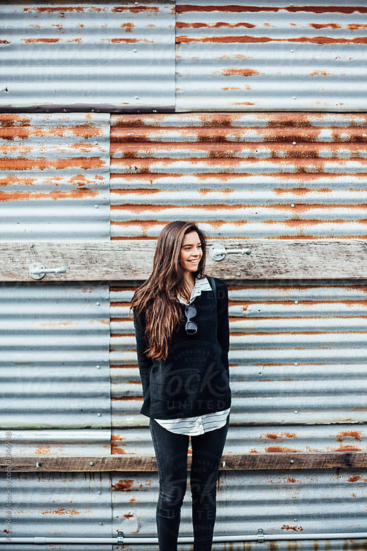 Woman standing against rusty tin wall by Kara Riley for Stocksy United