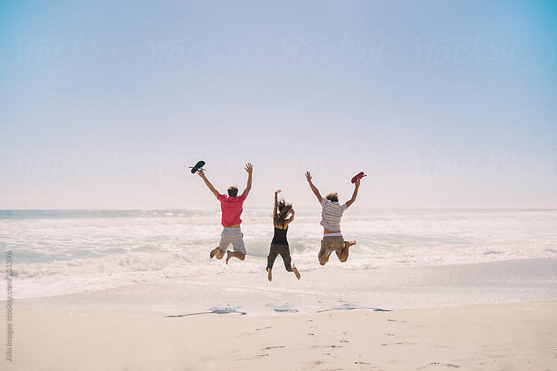 Friends jumping on the beach by Aila Images for Stocksy United