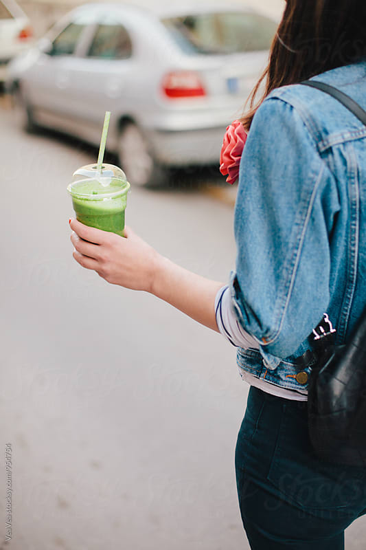 Woman drinking smoothie in the street by Marija Mandic for Stocksy United