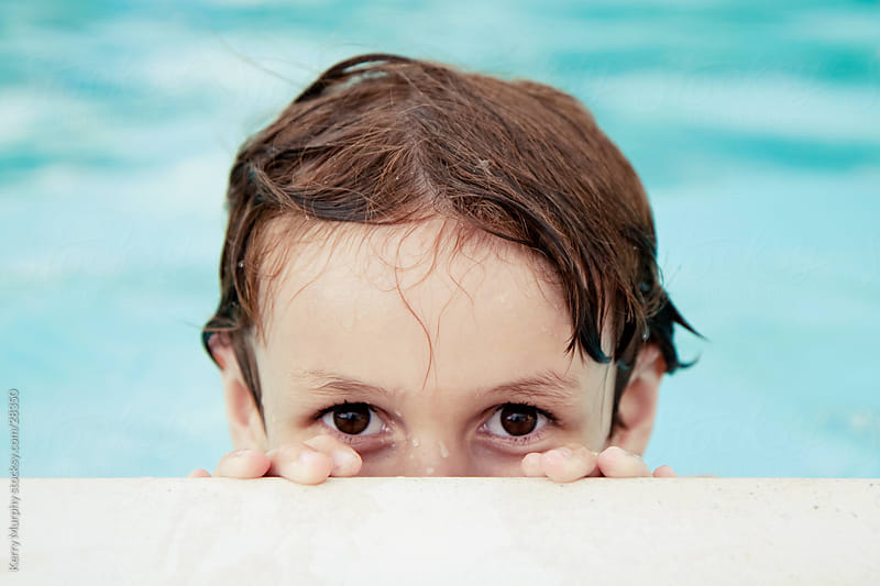 Young boy with brown eyes peeking over edge of pool by Kerry Murphy for Stocksy United