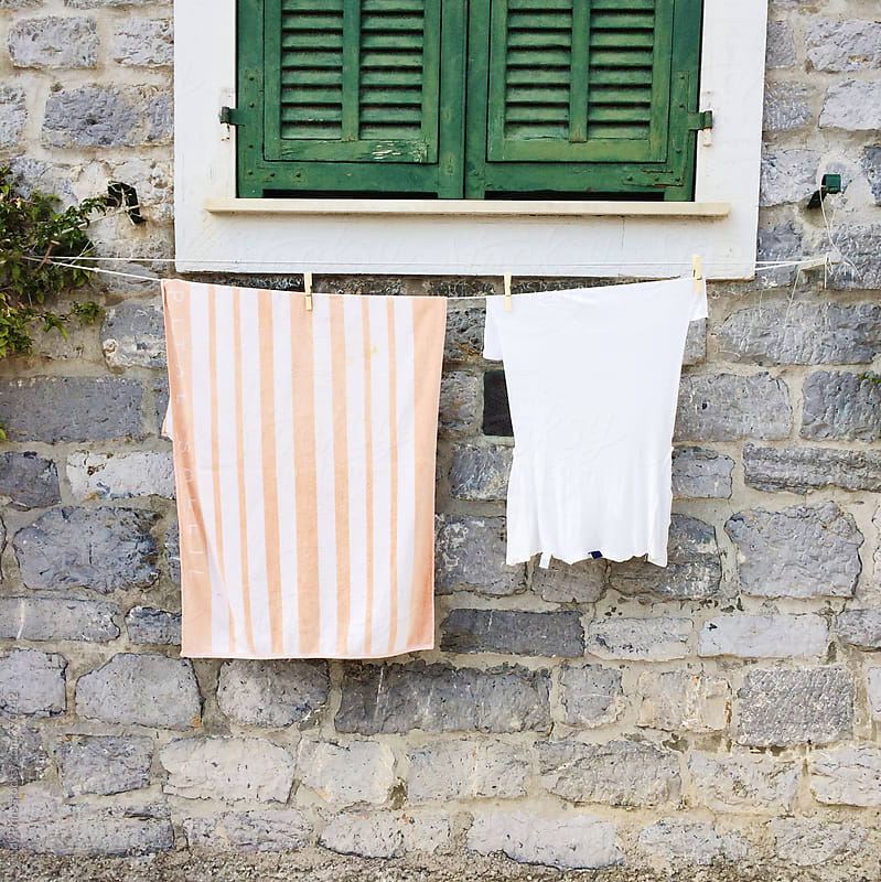 Green shuttered window with clean laundry hanging beneath by Cindy Prins for Stocksy United