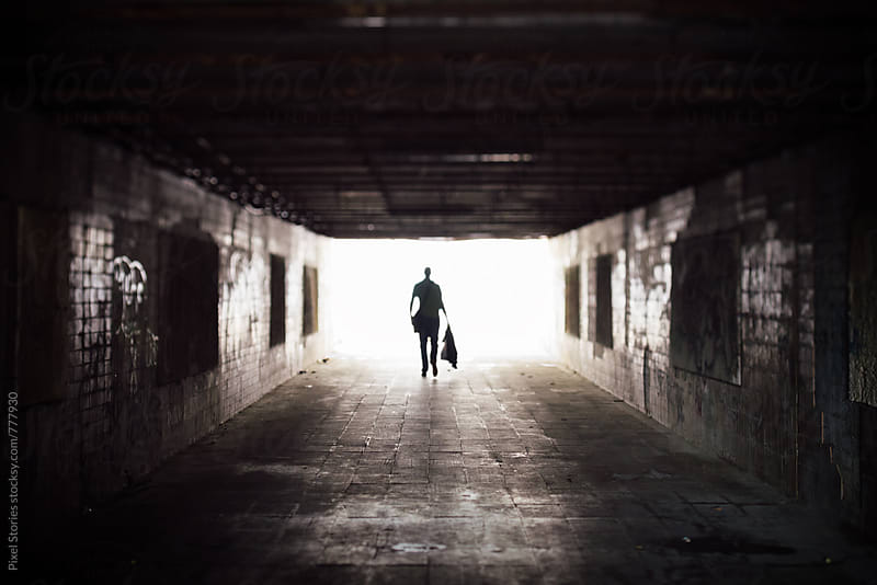 Silhouette of a man exiting an underpass by Pixel Stories for Stocksy United