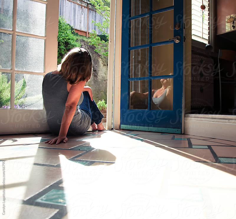 Woman sitting in a doorway looking out - her image reflected in the glass by Carolyn Lagattuta for Stocksy United