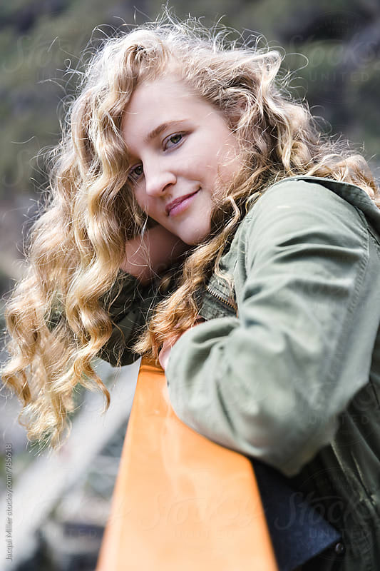 Teen girl, with long curly hair, looking at camera by Jacqui Miller for Stocksy United
