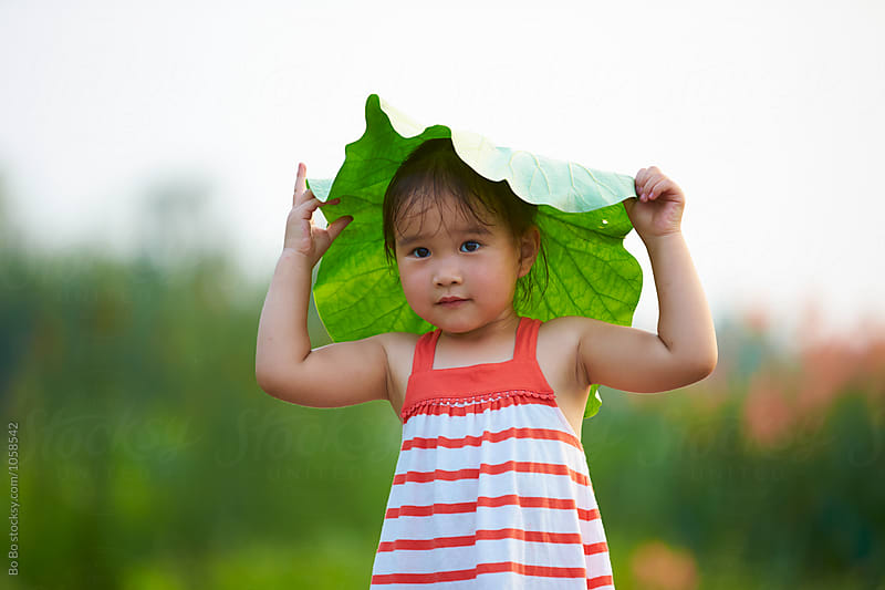 lovely little girl playing with lotus leaf outdoor by Bo Bo for Stocksy United