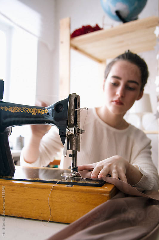 Close-up of seamstress sewing on vintage machine by T-REX & Flower for Stocksy United