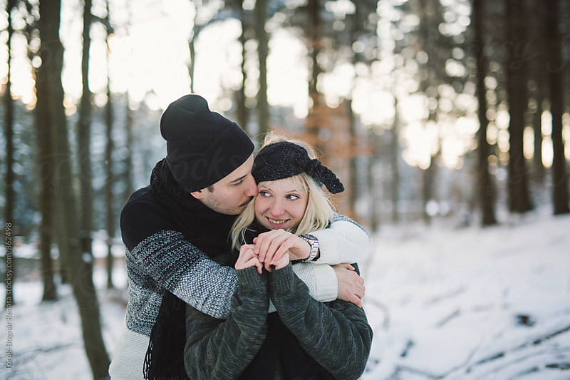 Lovely fashionable couple in the snowy woods by Török-Bognár Renáta for Stocksy United