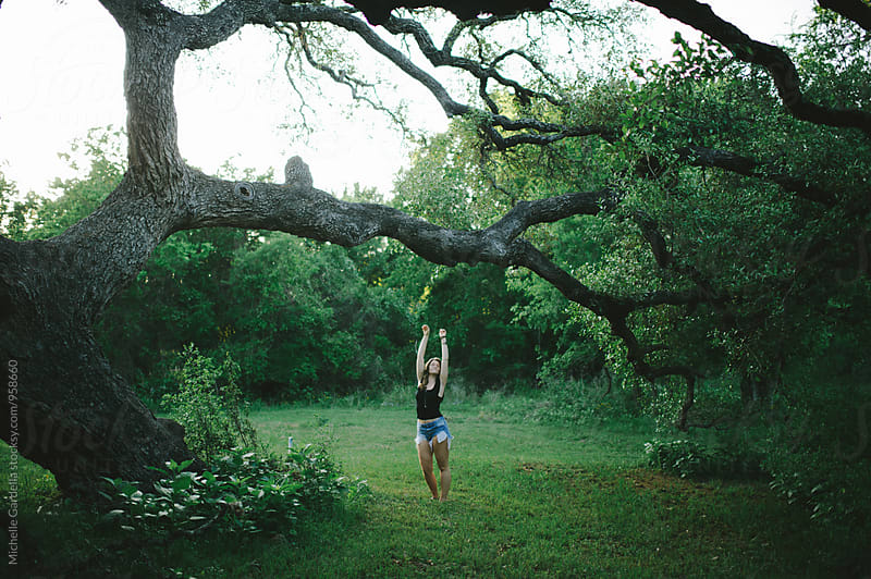 young woman reach for tree by Michelle Gardella for Stocksy United