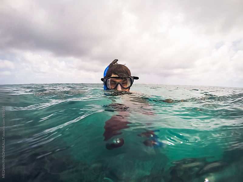 Man with Snorkel Mask in Tropical Green Water by MEGHAN PINSONNEAULT for Stocksy United
