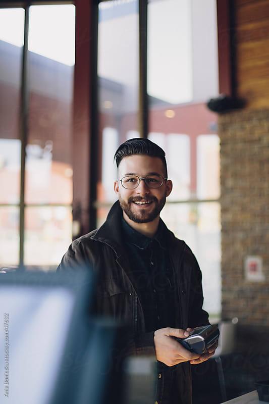 Smiling man using a debit machine by Ania Boniecka for Stocksy United