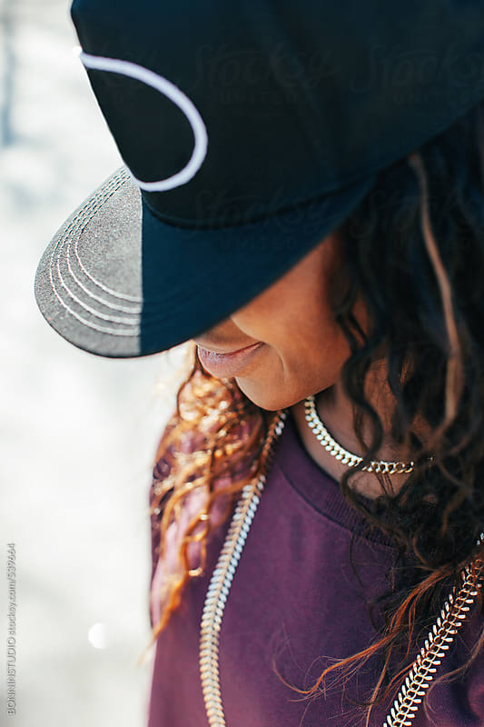 African american hip-hop style woman covering her face with a baseball cap. by BONNINSTUDIO for Stocksy United