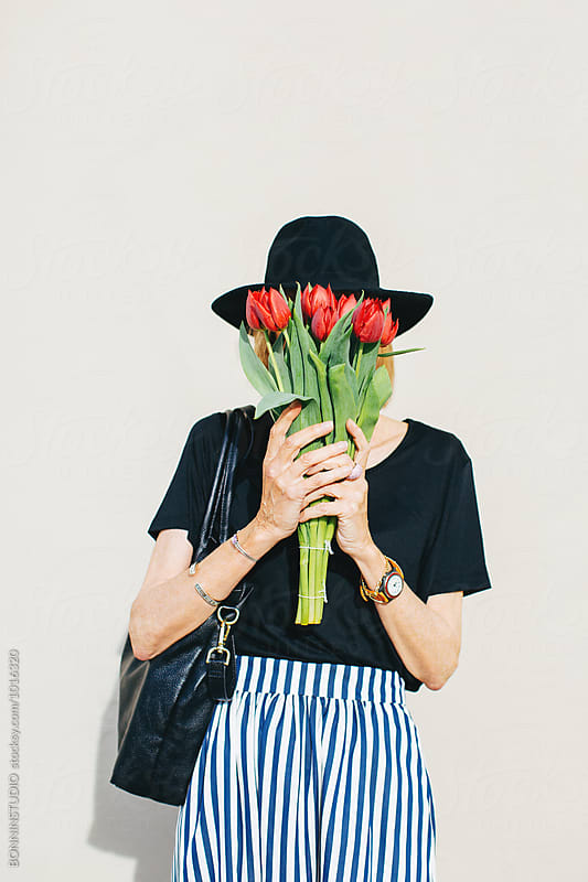 Stylish senior woman hiding her face with a bouquet of red tulips outside.  by BONNINSTUDIO for Stocksy United