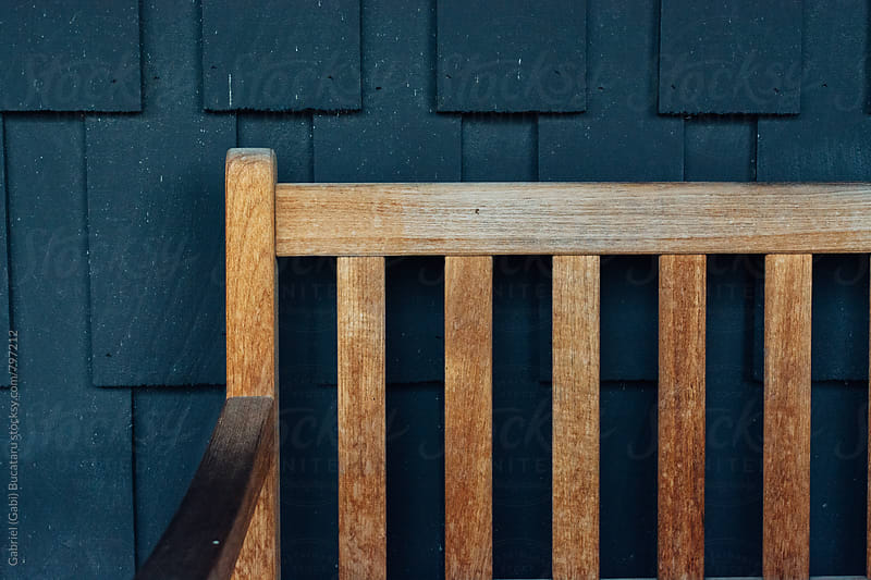Wooden outdoor bench next to a blue wall by Gabriel (Gabi) Bucataru for Stocksy United