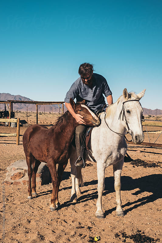 outdoorsman with two horses on a desert farm by Micky Wiswedel for Stocksy United