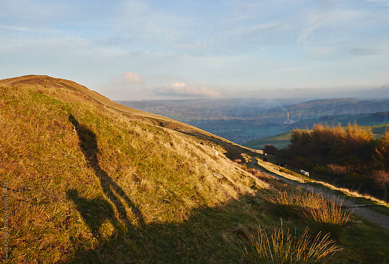 Shadow of a male and his dog on mountainside at sunset. Derbyshire, UK. by Liam Grant for Stocksy United