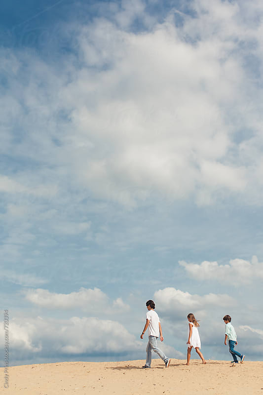 Three kids walking in the sand underneath a big blue sky by Cindy Prins for Stocksy United