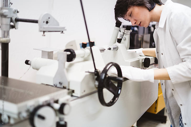 Female Scientist Looking Through the Microscope by Katarina Radovic for Stocksy United
