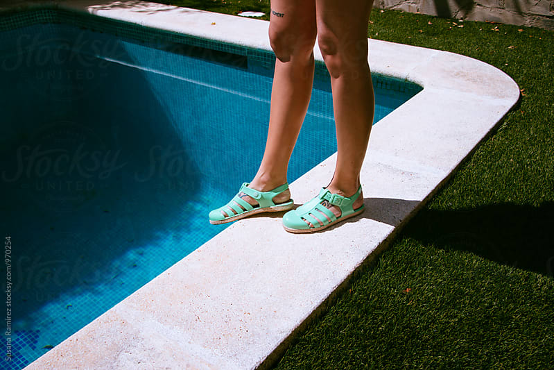 Woman's legs with sandals, on the edge of the pool by Susana Ramírez for Stocksy United
