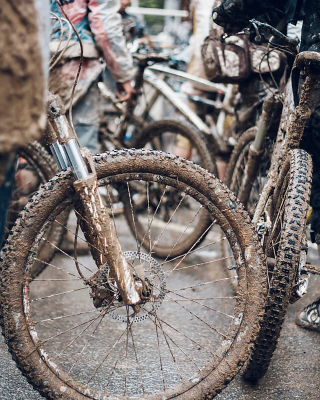 Close up of mountain bike covered on mud after a long race by Jordi Rulló for Stocksy United
