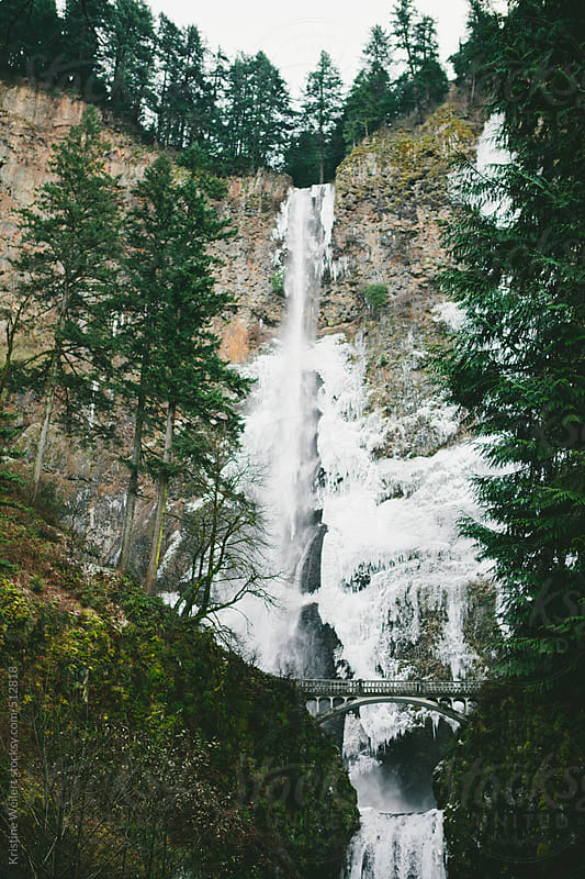 Beautiful frozen waterfall in the winter with a bridge by Kristine Weilert for Stocksy United
