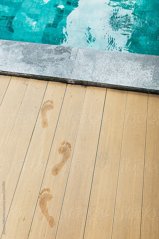 Wet feet traces at the wooden swimming pool side by Jovana Milanko for Stocksy United