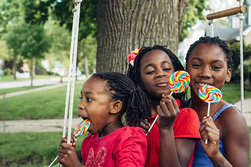 Three black girls on a swing with lollipops by Gabriel (Gabi) Bucataru for Stocksy United