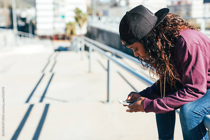 African american hip-hop style woman using phone in the city. by BONNINSTUDIO for Stocksy United
