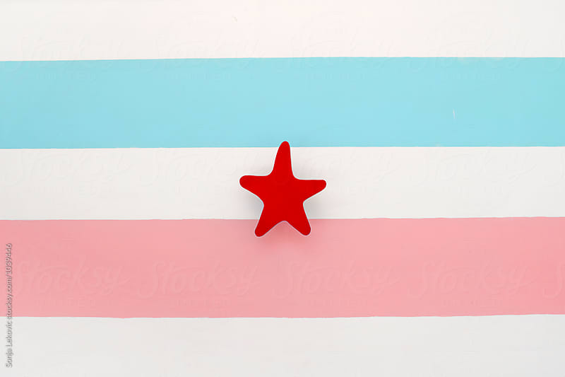 pastel flag with red star by Sonja Lekovic for Stocksy United