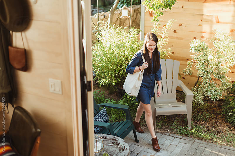 Young woman walking up to the door of her tiny home with reusable grocery bag by Kate Daigneault for Stocksy United