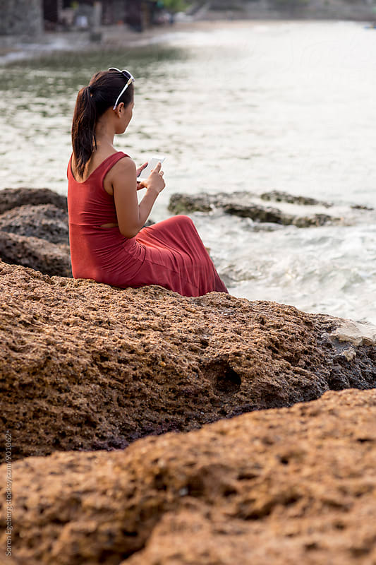 Beautiful girl in red dress using smart phone by the sea  by Soren Egeberg for Stocksy United