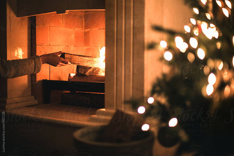 Woman Building a Fire in the Fireplace at Christmas by Lumina for Stocksy United
