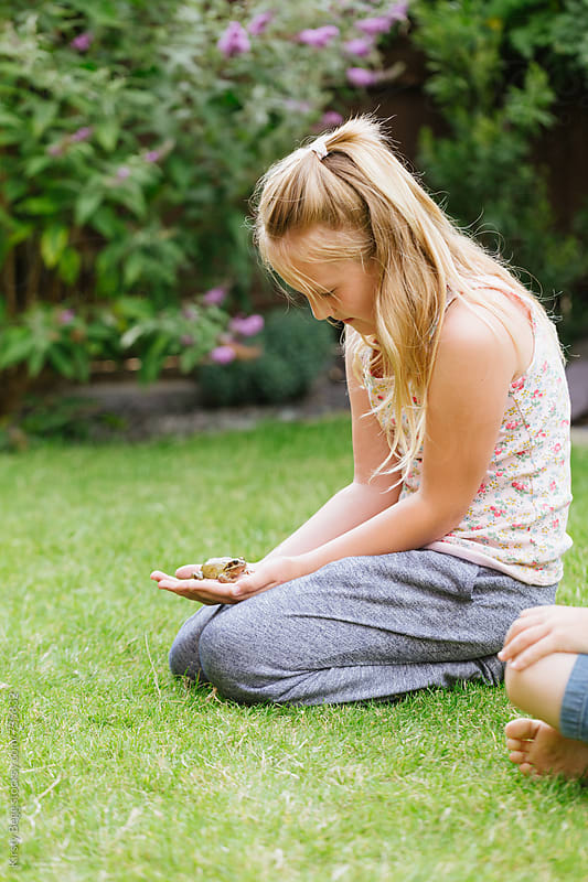 Girl holds frog in garden at home by Kirsty Begg for Stocksy United
